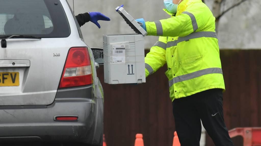ARCHIV - In einem Corona-Testzentrum wirft ein Fahrer aus dem Auto ein Testkit in eine Box. Die Bürger in England sollen sich bald zweimal pro Woche kostenlos auf das Coronavirus testen lassen können. Foto: Jacob King/PA Wire/dpa