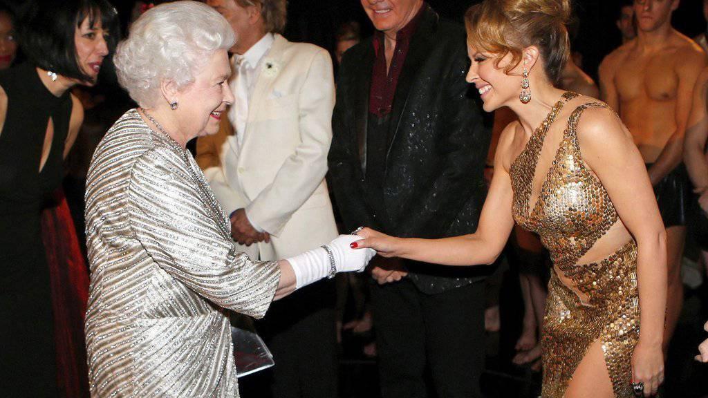 Queen Elizabeth II. (l) und Kylie Minogue (r) - hier 2012 nach einer Show in der Royal Albert Hall - sehen sich bald wieder: Minogue gehört zu den Künstlern, die der Königin am 15. Mai in einer Fernsehshow zum 90. Geburtstag gratulieren. (Archivbild)