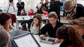 Tagungsteilnehmerinnen lassen sich die Arbeit am Tablet-PCvon Schülerinnen und Schülern erklären.
