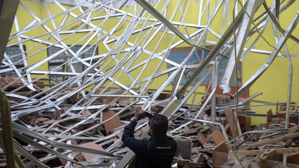 Ein lokaler Journalist filmt den Schaden an einem Klassenzimmer in einer Schule. Ein Erdbeben der Stärke 6,0 hat am Samstag den Osten der indonesischen Insel Java erschüttert. Foto: Hendra Permana/AP/dpa