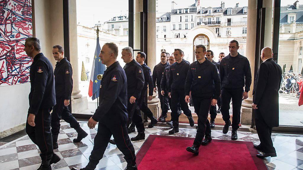 Feuerwehrleute von Notre-Dame im Élyséepalast empfangen