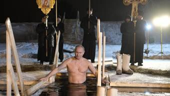 Aus Anlass des Epiphanias-Festes der orthodoxen Kirche: Der russische Präsident Wladimir Putin - umgeben von Popen und Ikonen - taucht bei minus fünf Grad Celsius in den Seliger-See nordwestlich von Moskau.