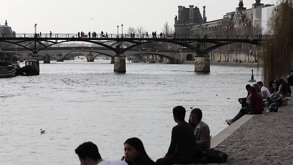 Menschen am Ufer der Seine in Paris. Foto: Lewis Joly/AP/dpa