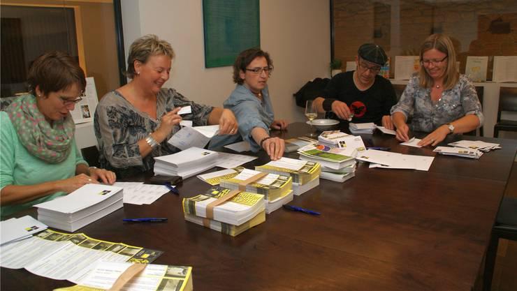 Die Vorstandsmitglieder von Pro Schöftland verpacken die Programme.