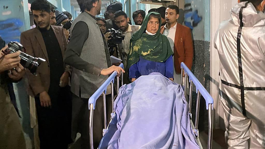 Der zugedeckte Leichnam einer Frau, die bei einem bewaffneten Angriff in der Stadt Dschalalabad in Afghanistan getötet wurde, wird auf einer Bahre transportiert. Foto: Sadaqat Ghorzang/AP/dpa
