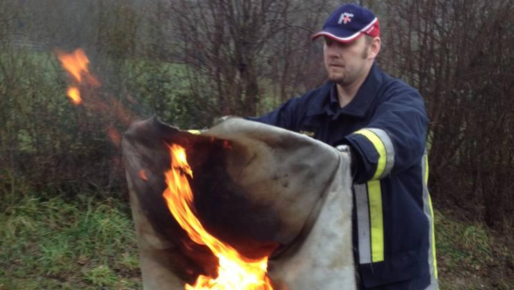 Feuerwehrkommandant Patrik Gfeller demonstriert, wie man einen brennenden Gegenstand mit der Branddecke löscht.