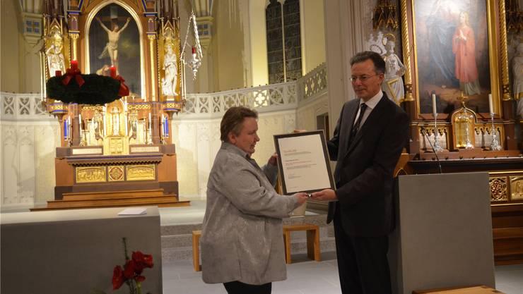 Kirchenpflegepräsidentin Cäcilia Schriber nimmt den Schweizer Denkmalpreis 2015 aus den Händen von Peter Omachen entgegen.