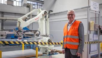 Geschäftsführer Matthias Ruch vor seinem neusten Mitarbeiter, einem mit viel Sensorik ausgerüsteten Roboter-Arm.