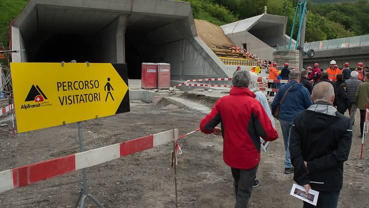 Besucher mit Schutzhelmen machen sich am Tunnelportal bereit für die Besichtigung im Ceneri Tunnel. (Archivbild)