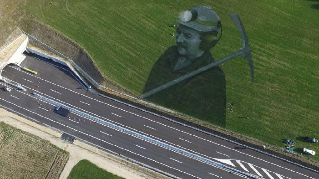 Mit dem Bild eines Bauarbeiters will Künstler Saype die Menschen würdigen, welche die Autobahn A16 bauten.