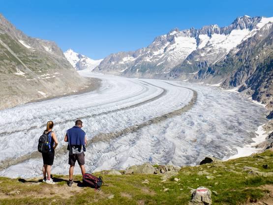 Zwei Wanderer blicken auf den Aletschgletscher im Wallis, der in den letzten Jahren stark zurückgegangen ist.