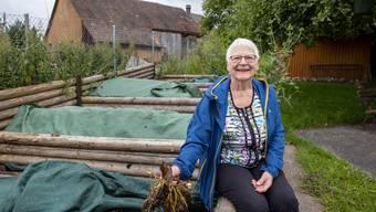 Rose Marie Begert sitzt auf einer der sechs holzgerahmten Kompostkammern.
