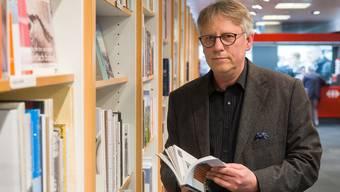 Jens Stocker, Eigentümer von «Bider & Tanner», in der Reisebuchabteilung – im Hintergrund die SBB-Schalter.
