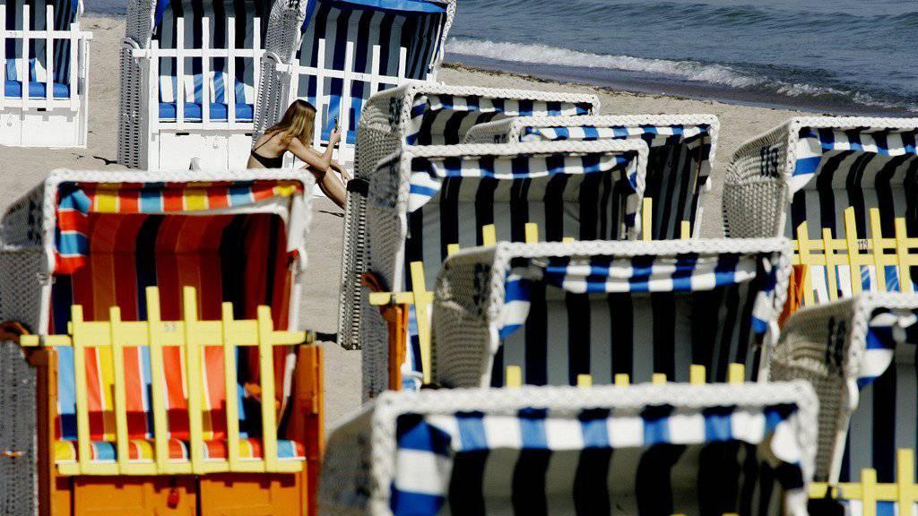 Eine Frau sitzt am Freitag, 27.April 2007, bei Temperaturen um die 25 Grad Celsius inmitten von Strandkoerben am Strand von Timmendorfer Strand an der Ostsee. Der April 2007 wird nach meteorologischen Hochrechnungen gleich mit mehreren Wetterrekorden in die Geschichte eingehen. Sowohl bei der Temperatur als auch bei der Sonnenscheindauer erwartet der Deutsche Wetterdienst (DWD) die hoechsten Werte seit Jahrzehnten. (AP Photo/Heribert Proepper) ---A woman sits among of beach chairs at the beach of Timmendorfer Strand at the Baltic Sea, northern Germany, as the temperature reaches 25 degrees centigrade (77  Fahrenheit) on Friday, April 27, 2007. (AP Photo/Heribert Proepper)