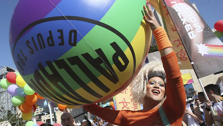 Die Teilnehmer gehen während einer Pride Parade durch eine Straße. Foto: Chiang Ying-Ying/AP/dpa