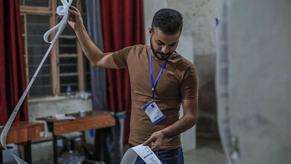 Ein Mitarbeiter des Wahlausschusses zählt Stimmen für die irakischen ParlamentsEin Mitarbeiter des Wahlausschusses zählt Stimmen für die irakischen Parlamentswahlen in einem Wahllokal aus. Unter einem Grossaufgebot an Sicherheitskräften hat im Irak am Sonntag die Parlamentswahl stattgefunden.wahlen in einem Wahllokal aus. Unter einem Großaufgebot an Sicherheitskräften hat im Irak am Sonntag (10.10.21) die Parlamentswahl stattgefunden. Foto: Ameer Al Mohammedaw/dpa