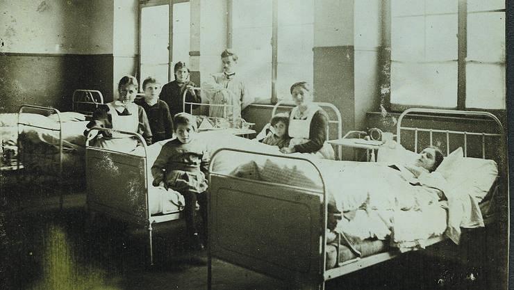 1918 ist das Pratteler Schulhaus Grossmatt ein Notspital. Primarlehrer Ernst Zeugin (am Fenster) hilft den Pflegerinnen.  Staatsarchiv Baselland