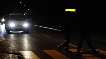 Eine gefährliche Situation: Dunkel gekleidete Fussgänger sind für Autofahrer kaum sichtbar.