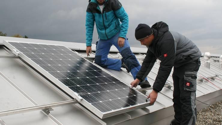 Die Monteure der Firma Wyder montieren die Solarpanels auf dem Dach des Gemeindehauses.