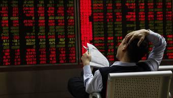 Ein Investor in Peking schaut sich am Donnerstag die Aktienkurse an. (Symbolbild)