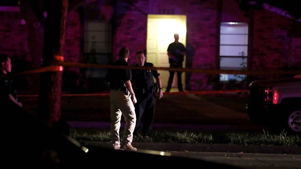 Polizisten untersuchen das Haus, in dem sieben Menschen durch die Waffe eines Mannes ums Leben gekommen sind. Der Täter wurde später von der Polizei erschossen.