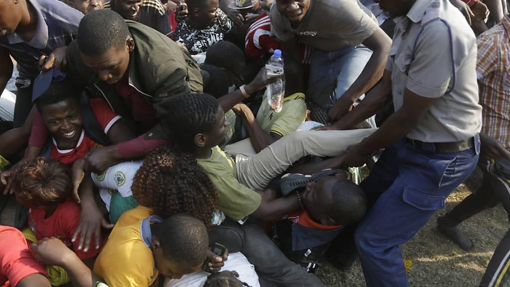 Chaotische Szenen bei der Aufbahrung von Robert Mugabe im Rufaro Stadium in Harare: Ein Polizist versucht Ordnung zu schaffen.