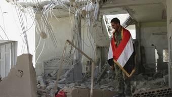 Ein Mann mit einer syrischen Flagge um die Schultern steht in einem zerstörten Haus in der Provinz Hama.