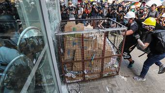 Mit einem Rollwagen aus Metall zertrümmert eine Gruppe von Demnonstranten eine Scheibe und stürmt das Parlament in Hongkong.