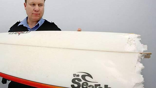 Polizist mit dem Surfbrett des Opfers, das der Hai in Stücke riss