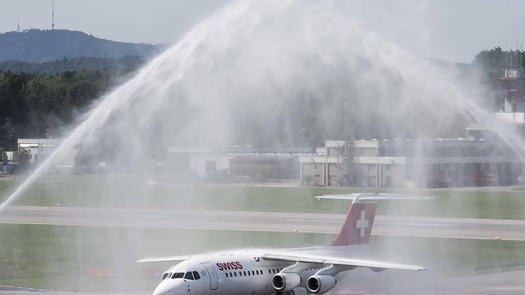 Eine Wasserfontäne zum Abschied: Der Avro RJ100 Jumbolino nach seinem letzten Flug von Genf nach Zuerich. (KEYSTONE/Ennio Leanza)