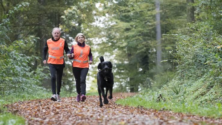 Die blinde Beatrice Acuna kann Dank ihrem Laufpartner Jean Bläuenstein fast ganz normal im Wald joggen, und Blindenhung Maverick freut's auch.