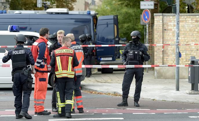 Polizei und Hilfskräfte vor dem jüdischen Friedhof in Halle. (AP Photo Jens Meyer)