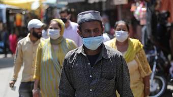 Passanten gehen mit Mundschutz über einen Markt in Jammu. Foto: Channi Anand/AP/dpa