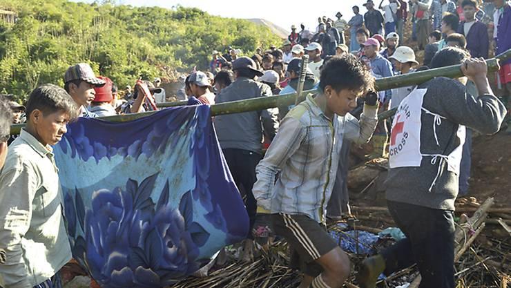 Rotkreuz-Mitarbeiter bergen Opfer des Erdrutsches in Myanmars. Die Chance, Überlebende zu finden, ist minim.