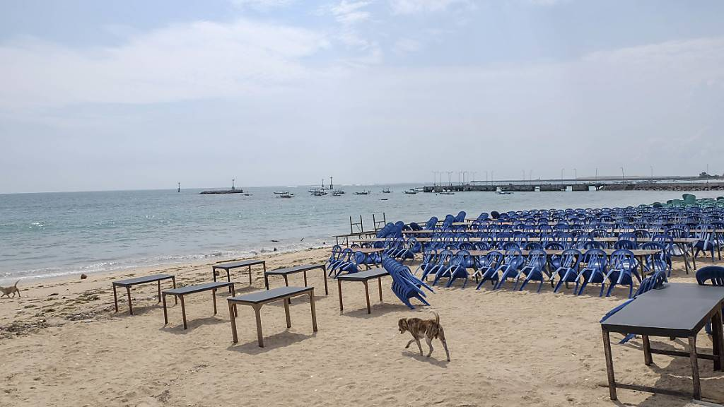 ARCHIV - Ein Hund läuft am Jimbaran Beach zwischen Tischen eines leeren Fischrestaurants. Als «Insel der Götter» ist Bali bei Surfern, Badegästen und Yogis aus aller Welt bekannt. Wegen Corona liegt die Reisebbranche seit Monaten am Boden. Foto: Wawan Kurniawan/XinHua/dpa