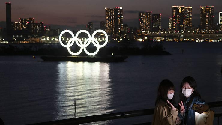 Zwei Frauen machen in Tokio ein Selfie mit den leuchtenden Olympia-Ringen