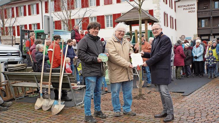 Hanspeter Hilfiker (r.) übergibt Jürg Link die Urkunde zur Baumpflanzung. Links Thomas Baumann vom Naturama Aargau.