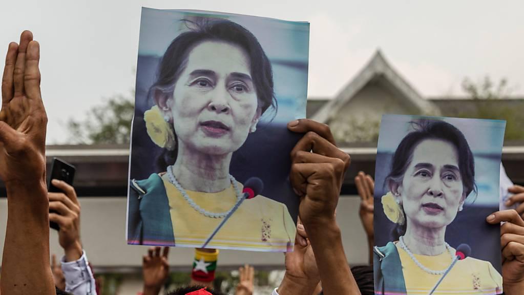 ARCHIV - Demonstranten halten während eines Protests gegen den Militärputsch in Myanmar Bilder von Aung San Suu Kyi. Foto: Andre Malerba/ZUMA Wire/dpa