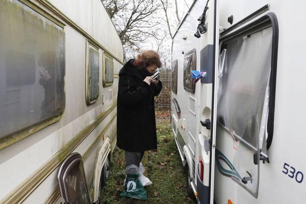 Trudy Imholz fotografiert die Schäden. Um ihre Schuhe zu schützen, hat sie Plastiksäcke übergezogen.