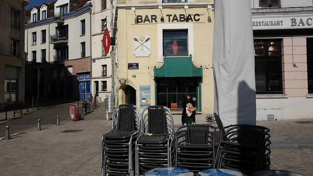 Stühle sind in einer leeren Fußgängerzone vor einem Café aufeinandergestapelt. Frankreich verhängt im Kampf gegen die Corona-Pandemie regionale Ausgangsbeschränkungen. Foto: Michel Spingler/AP/dpa