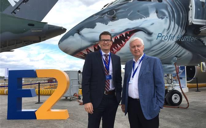 Im Angriffsmodus: Martin Ebner und Tobias Pogorevc (links), CEO von Helvetic Airways, gaben diese Woche an der Aviatikmesse im englischen Farnborough den Kauf von bis zu 24 Flugzeugen des Typs E2 des brasilianischen Herstellers Embraer bekannt – im Bildhintergrund mit Hai-Bemalung. Gemäss Listenpreis würde dieser Deal 1,5 Milliarden Dollar kosten. Für die Schweizer Airline ist dies ein neuer Meilenstein.