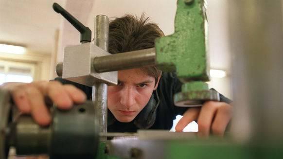 Ein Lehrling bei der Arbeit an der Maschine im Unterricht an der Abteilung Lehrwerkstätte für Möbelschreiner an der baugewerblichen Berufsschule Zürich.