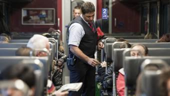 Ein Zugbegleiter kontrolliert Billette in einem SBB-Zug (Bild wurde vor Corona gemacht.))