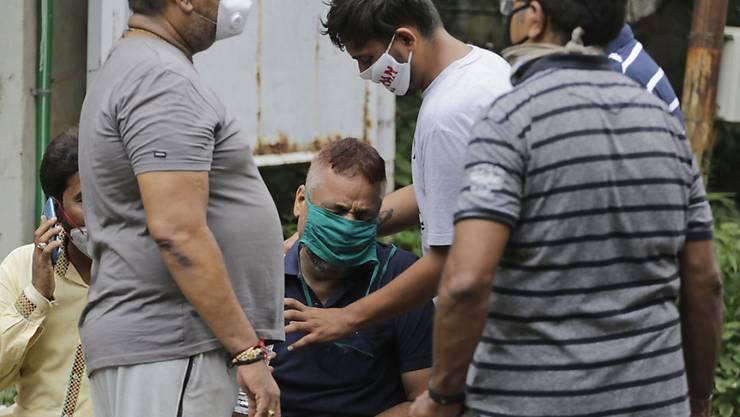 Angehörige von Patienten warten vor dem Shrey-Krankenhaus, wo am frühen Morgen ein Feuer ausbrach, auf Neuigkeiten. Foto: Ajit Solanki/AP/dpa