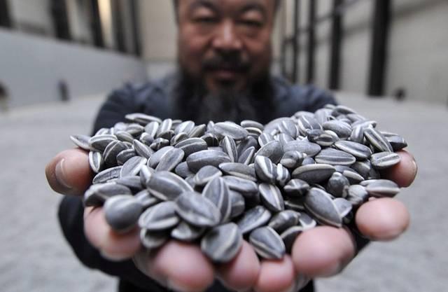 Ai Weiwei präsentiert eine Handvoll Sonnenblumenkerne aus Porzellan - Der Künstler soll in China Steuern nachzahlen (Archiv)