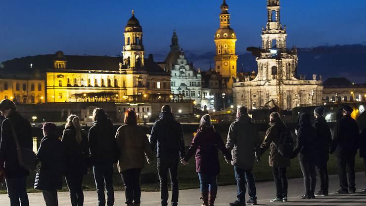 Menschenkette vor der Kulisse der wiederaufgebauten Dresdner Altstadt am Elbe-Ufer mit Stadtschloss (Mitte) und Hofkirche (rechts).