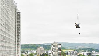 Helikopter liefert Bagger aufs Hochhaus vom Spital Limmattal