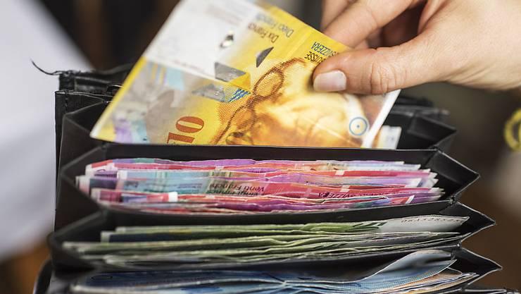 Pralles Portemonnaie mit eigenem und fremdem Geld: Schweizer bleiben laut einer Studie weltweit am reichsten. Gleichzeitig weisen sie die höchste Schuldenlast pro Kopf auf.