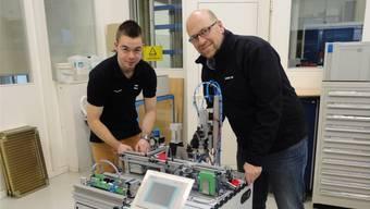 Tobias Blum (links) und Daniel Christen erklären anhand eines Automatendie möglichen Aufgaben der Meisterschaftsteilnehmenden.