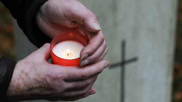 Eine Frau zündet eine Kerze an für einen Verstorbenen (Symbobild)